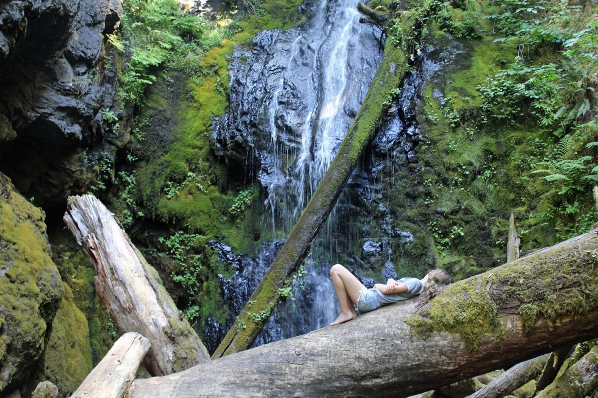 Girl lying on her back, enjoying the peace of Trestle Creek Waterfall